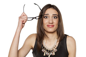 confused young woman with glasses in her hand
